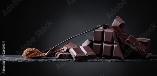 obraz dibond Broken chocolate pieces and cocoa powder on black background.