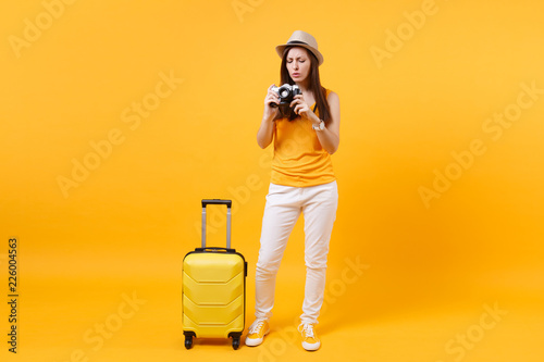 Fotografie, Obraz  Tourist woman in summer casual clothes, hat with suitcase, retro vintage photo camera isolated on yellow orange background