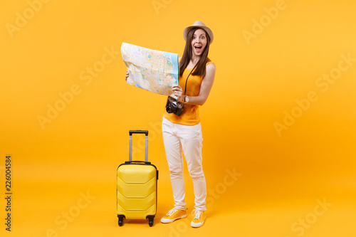 Foto  Traveler tourist woman in summer casual clothes, hat with suitcase, city map isolated on yellow orange background