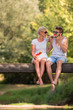 canvas print picture couple enjoying watermelon while sitting on the wooden bridge