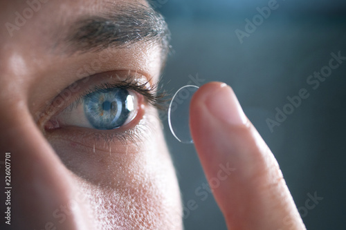 Obraz Close-up of a man putting contact lenses on blue eye. Concept of: healtcare, optic, hydration of the eye. - fototapety do salonu