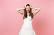 canvas print picture - Portrait of irritated dissatisfied bride woman in white wedding dress standing screaming clinging to head isolated on pink pastel background. Wedding celebration concept. Copy space for advertisement.