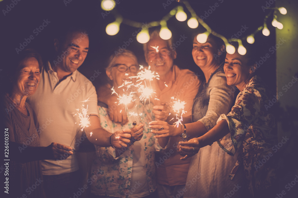 Fototapety, obrazy: group of caucasian people friends with different ages celebrate together a birthday or new year eve by night outdoor at home. lights and sparkles  with cheerful women and men having fun in friendship