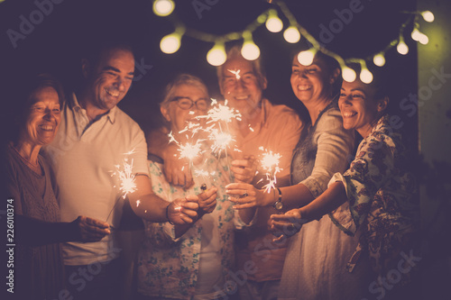 Fototapeta group of caucasian people friends with different ages celebrate together a birthday or new year eve by night outdoor at home. lights and sparkles  with cheerful women and men having fun in friendship obraz