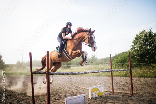 Young female jockey on horse leaping over hurdle Fototapeta