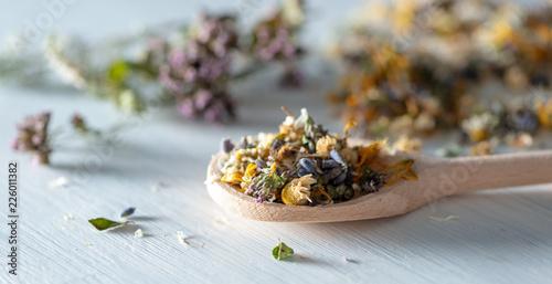 Fotografie, Obraz  Getrocknete Kräuter und Blüten auf einem Holzlöffel-Homöopathie, alternative Küc