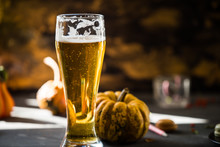 Glass Of Golden Beer On Dark, Wooden Table, Surrounded By Autumn Decorations, Pumpkins, Leaves