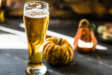 Glass Of Golden Beer On Dark, Wooden Table, Surrounded By Autumn Decorations