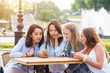 Four attractive young women use smartphones at a table in the Park