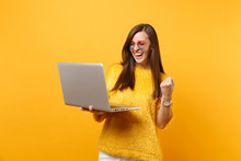 Laughing Young Woman In Sweater, Heart Eyeglasses Doing Winner Gesture Working On Laptop Pc Computer Isolated On Bright Yellow Background. People Sincere Emotions, Lifestyle Concept. Advertising Area.