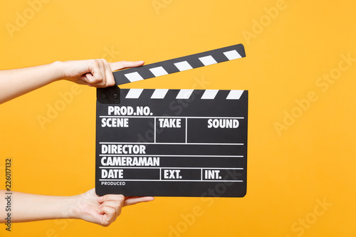 Close up female holding in hand classic director clear empty black film making clapperboard isolated on trending yellow orange background Tablou Canvas