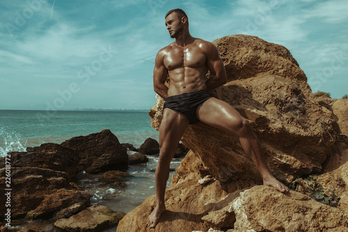 Photographie  Strong face muscle male model on the nature background with sand stones and wate