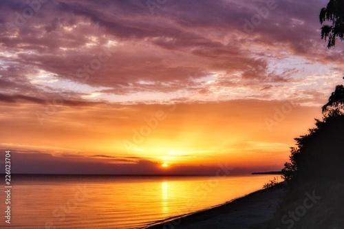 Fototapeta plaża o wschodzie słońca nad morzem obraz