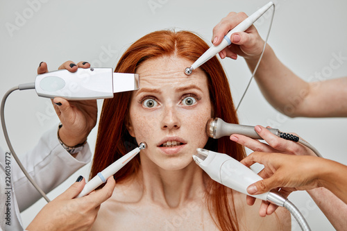 Fotografie, Obraz  Several beauticians doing cosmetology procedures using medical tools all together at the same time on scared and shocked female face