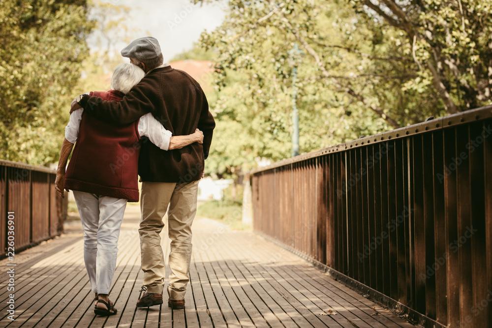 Fototapeta Senior couple in warm clothing walking together in park