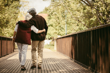 Senior couple in warm clothing walking together in park