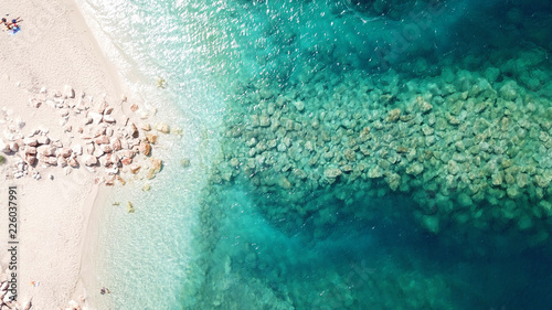 Aerial drone bird's eye view of famous and exotic sand tongue beach with clear emerald waters near castle of Santa Mavra in entrance of Lefkada island, Ionian, Greece