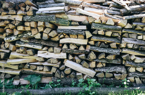 Natural firewood lying in a pile outdoors in the grass. Wood background texture. Eco friendly wallpaper.