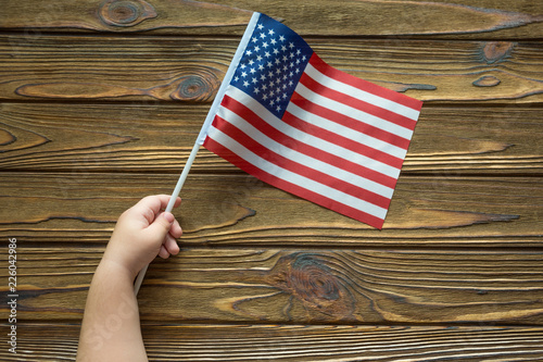 A child's hand holds the flag of the United States of America. Wooden background. Patriotism, Independence Day, July 4th, holiday. Close-up