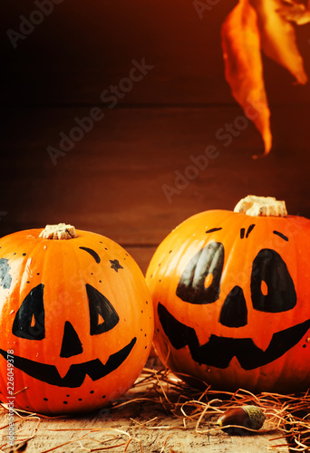 Poster Halloween festive composition with smiling pumpkins guards, lantern, straw and fallen leaves on dark wooden background, rustic style, selective focus