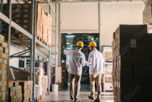 Father and son standing in their warehouse with helmets on their heads and looking at package prepared for transport Tapéta, Fotótapéta