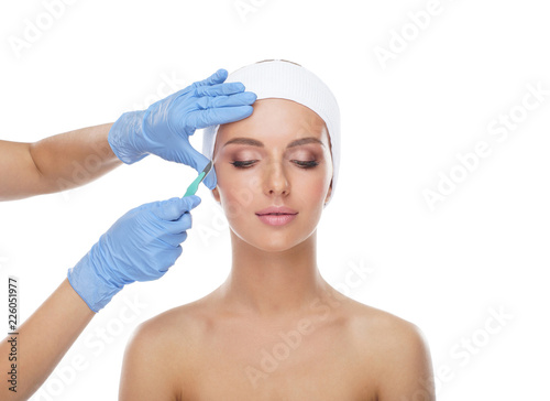 Foto Beautiful face of the young woman and the medical scalpel in doctor's hands isolated on white