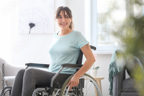 Obraz Happy young woman in wheelchair at home - fototapety do salonu