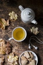 Cozy Autumn Still Life On A Wooden Background - Green Tea, Whole Grain Biscuits, Headphones, Dry Maple Leaves. Top View, Flat Lay