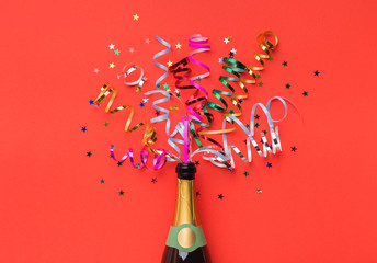 Champagne bottle with colorful streamers top view