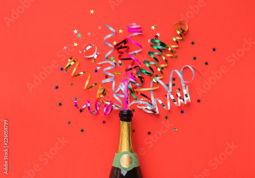 Spoed Fotobehang Carnaval Champagne bottle with colorful streamers top view