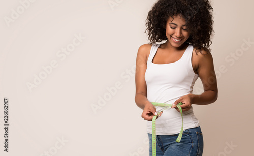 Obraz African-american woman measuring waist and looking on tape - fototapety do salonu