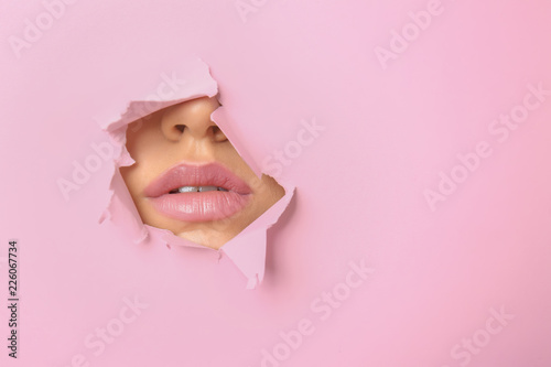Fotografía  Lips of beautiful young woman visible through hole in pink teared paper