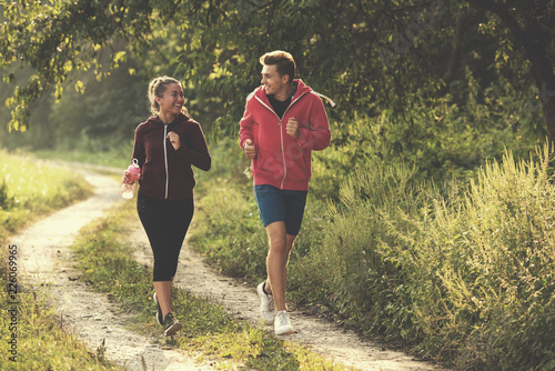 Foto op Canvas Jogging young couple jogging along a country road