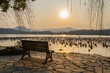 Empty bench overlooking sunset over West Lake in Hangzhou