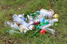 Rubbish Such As Plastic And Glass Bottles, Tins, Cans And Pieces Of Paper On Grass