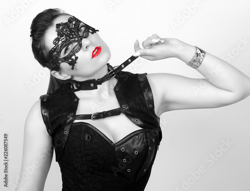 Fototapety, obrazy: Black and white Portrait of an adult sexy girl in a mask and with red lips in leather clothes on a gray background