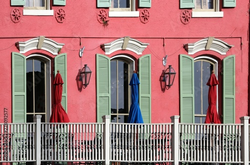 green shutters on ornate window doors in red masonry wall with red and blue umbrellas on balcony, New Orleans, LA, USA