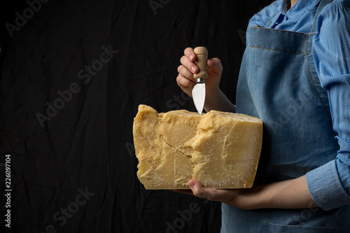 Woman holding knife and a slice of parmesan cheese on black background