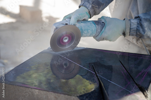 The work of the stone sculptor gabbro granite. stone cutting by grinding machine. dusty work
