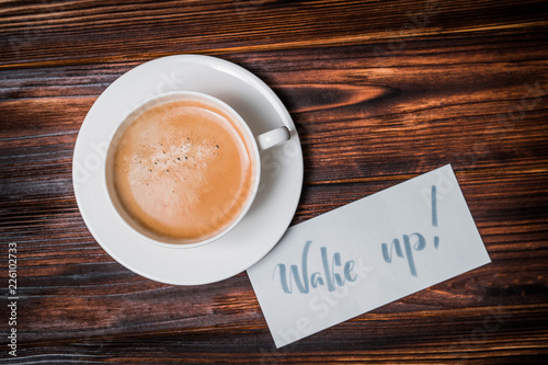 Foto op Plexiglas Chocolade Wake up text near cup of coffee. Font of lettering word on white paper by calligrapher. Morning, handwriting, lettering, concept.