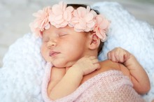 Cute And Adorable Newborn Caucasian Girl Smiling In Her Sleep. Pink Head Band With Flowers And A Light Blanket, Newborn Photo Session Concept.