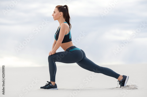 Fototapeta Fitness woman doing lunges exercises for leg muscle workout training, outdoor