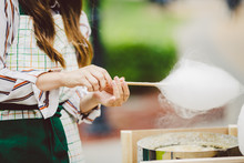 Theme Is A Family Small Business Cooking Sweets. Hands Close-up Young Woman Trader Owner Of The Outlet Makes A Candy Floss, Fairy Floss Or Cotton Candy In The Park In Summer