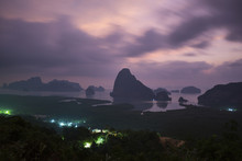 Scenic View Of Limestone Rocks In Sea Against Cloudy Sky At Dusk