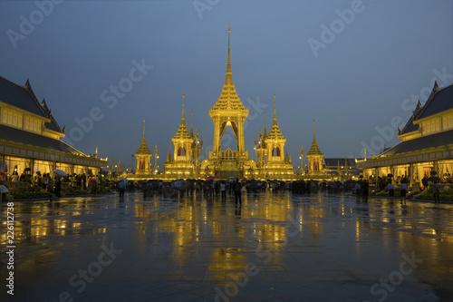 Tourists visiting illuminated royal crematorium against cloudy sky at dusk