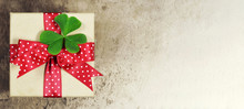 Gift Box With Red Ribbon And Clover On Grunge Background With Copy Space