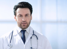 Portrait Of Serious Doctor On Blurred Background