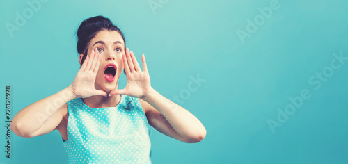 Young woman shouting on a solid background Wallpaper Mural