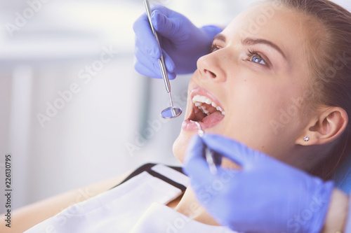 fototapeta na szkło Young Female patient with open mouth examining dental inspection at dentist office.