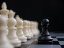 Strategic Planning Business Competition Concept. Black Pawn Surrounded By White Chess Pieces On A Chess Board